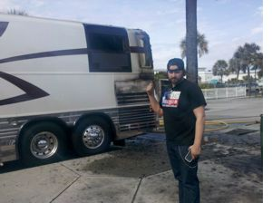 Randy Houser points to damage suffered moments before in bus fire.